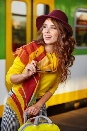 travel woman: Pretty young woman at a train station (autumn toned image)