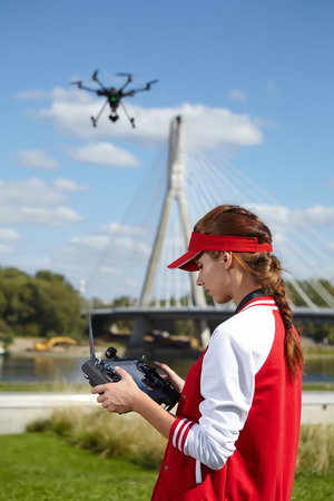 spying: Woman with remote control and flying surveillance drone