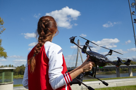 filmmaker: woman holding  drone uav over a field. Aerial video and photography maker.