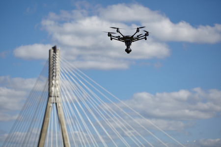 bridges: Copter flight against the blue sky. RC aerial drone. Stock Photo