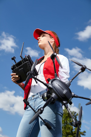 filmmaker: A woman is standing and holding drone over sky