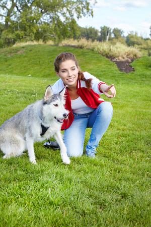 amigos abrazandose: niña y perro jugando al aire libre
