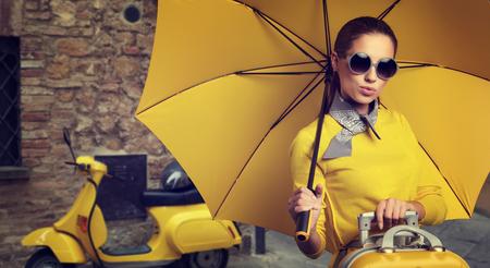 valise voyage: Femme élégante avec un Voyage de valise et parapluie sur la rue de la ville italienne Banque d'images