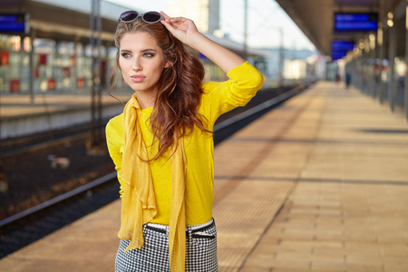 style woman: pretty adult woman with a suitcase near the train on the platform. Stock Photo