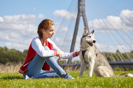 endear: Girl playing with her  dog in city park
