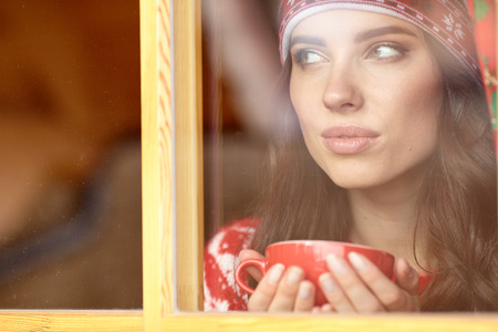 woman window: woman drinking coffee and looking out of the window on winter day.