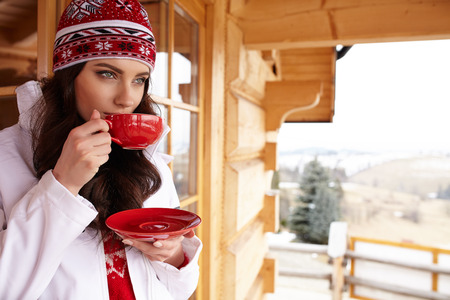 one woman: Young woman wearing a sweater and a white hat holding a cup of warm drink outdoors.
