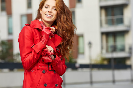 stylish hair: Beautiful stylish woman in a red coat. The city in the background Stock Photo