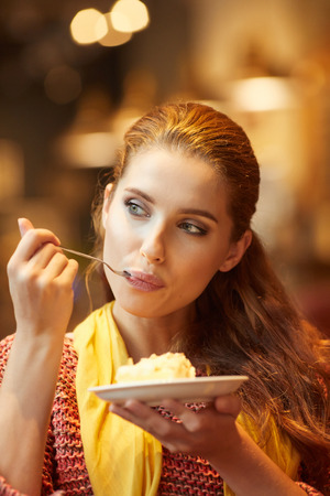 colores calidos: Young beautiful woman in a cafe eating cake. Warm colors.
