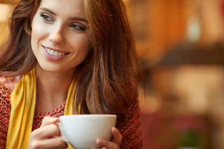 colores calidos: Young beautiful woman in the cafe. Warm colors.