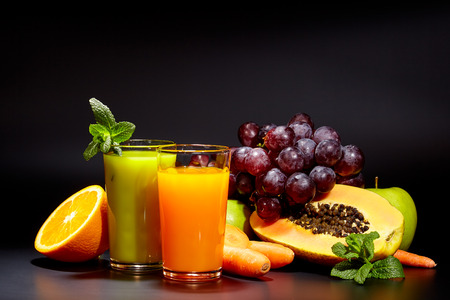 fruits juice: Glasses with fresh organic vegetable and fruit juices isolated on black. Detox diet. Stock Photo