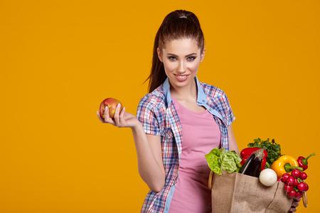 verduras verdes: mujer joven con verduras en bolsa de la compra, aislado en amarillo