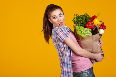 woman eat: beautiful young woman with vegetables in shopping bag, isolated on yellow Stock Photo