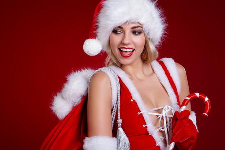 Glimlachend meisje in kostuum van de Kerstman Stockfoto