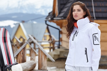 sports clothing: Woman snowboarder . winter day. Beautiful girl on snobord in the snow.