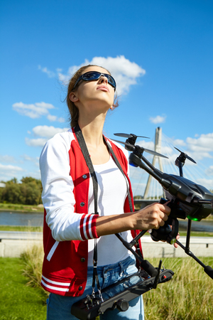 A woman is standing and holding drone Stock Photo