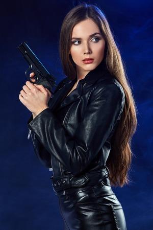 beautiful sexy girl holding gun . smoke background . Stockfoto