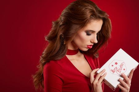 Mujer hermosa bodega regalo retrato en color de estilo de Navidad. Muchacha feliz sonriente sobre fondo rojo. Foto de archivo