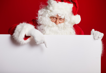 holding blank sign: Santa Claus pointing in blank advertisement banner isolated on red background with copy space