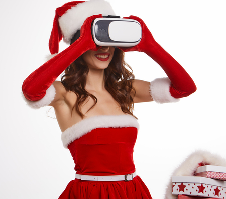 christmas, x-mas, winter, happiness concept - Beautiful young brunette with long hair in santa helper hat wearing virtual reality headset over white  background