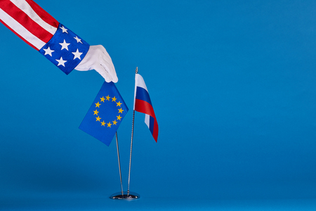 Two flags and hand on a blue background, the political concept