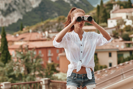 using binoculars: Portrait of a tourist woman using binoculars as she checks out the landscape