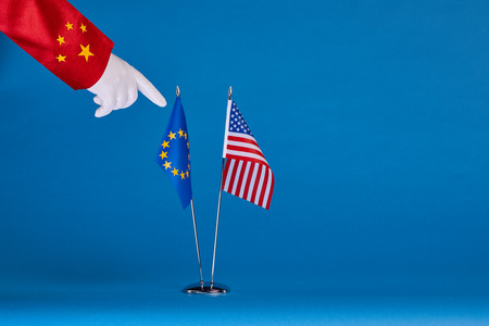 EU: Two flags and hand on a blue background, the political concept