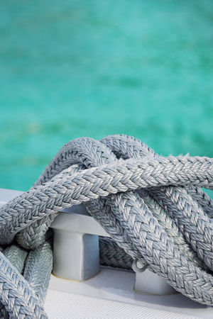 Coiled rope tied the knot on Edge of the boat .Light background tablets Reflections on the sea. Stock Photo