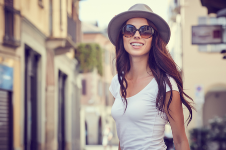 Close-up Fashion woman portrait of young pretty trendy girl posing at the city in Europe,summer street fashion,holding retro fedora hat popular until the 60s.laughing and smiling portrait. Stock Photo