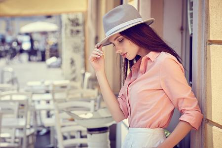 Beautiful young woman walking in the city. Fashion.