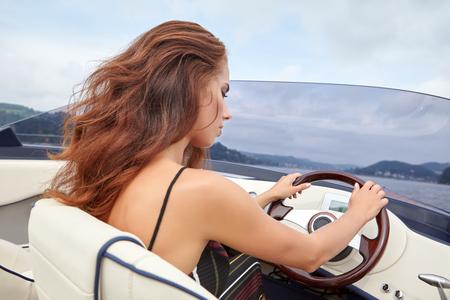 Zomervakantie - jong meisje het besturen van een motorboot
