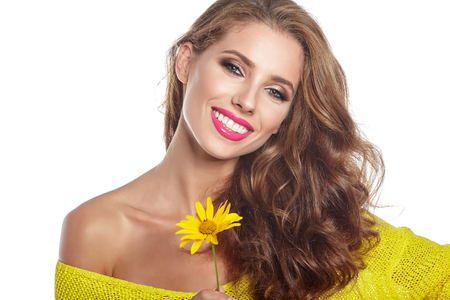 Portrait of young beautiful woman with stylish make-up and sunflower