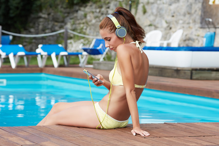 sexy pictures: Happy smartphone woman relaxing near swimming pool listening with earbuds to streaming music. Beautiful girl using her mobile phone