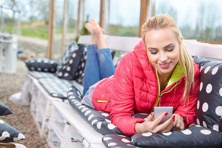 Attractive young blonde woman typing on phone on terrace . Sunny morning, relaxing time Stock Photo