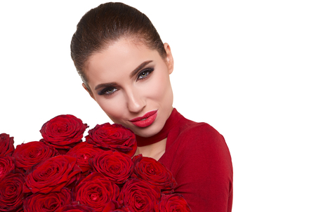 Beautiful model posing with red roses in the studio. Stock Photo
