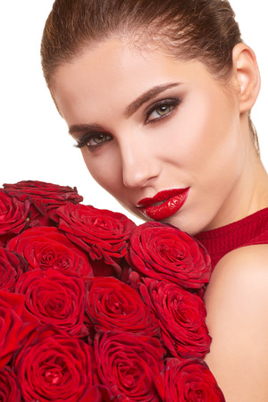 rosas rojas: Modelo hermoso que presenta con las rosas rojas en el estudio. Día de San Valentín