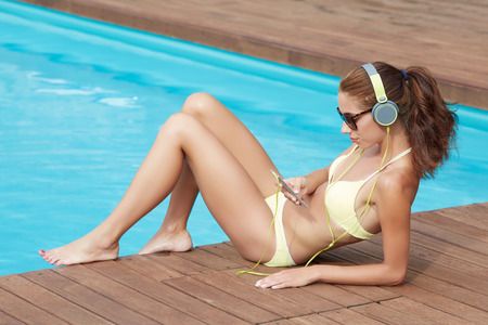 suntanned: Sexy woman in the yellow bikini on the sun-tanned slim and shapely body is posing near the swimming pool