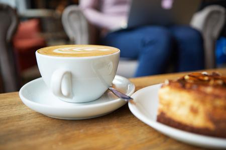 capuchinos: Dos tazas de café y pastel sobre la mesa, latte art