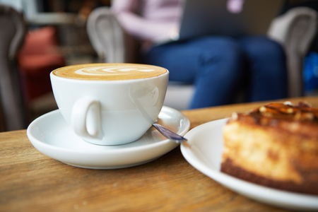 coffee table: Two cups of coffee and cake on the table, latte art