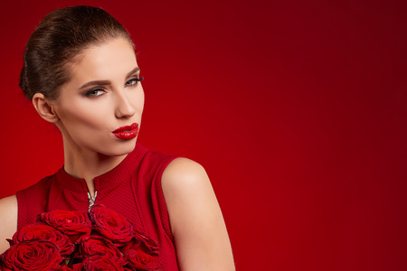 Beautiful surprised woman with red lips posing with flowers in the studio on a valentines day  background.