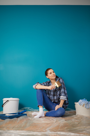 housepainter: Portrait of female painter near wall before painting. Stock Photo