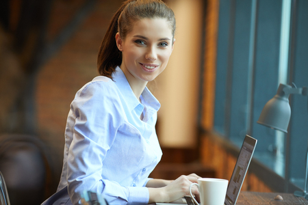 working place: Nice day! Young beautiful woman holding coffee cup and sitting at her working place