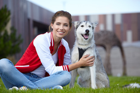 mujer perro: Woman playing with her dog outdoors