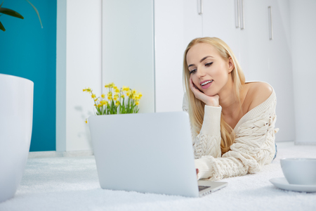 figuring: Young woman using laptop on bedroom
