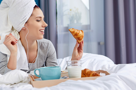 Girl with a towel on her head eating breakfast in bed Stock Photo