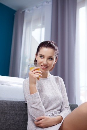 Portrait of a happy smiling latino hispanic woman eating a healthy breakfast in bed. Stock Photo