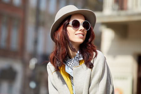 Close-up Fashion woman portrait of young pretty trendy girl posing at the city in Europe,summer street fashion,holding retro fedora hat popular until the 60s.laughing and smiling portrait.trendy