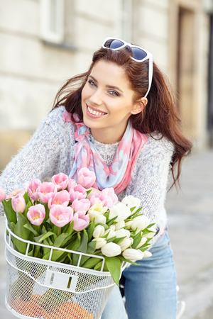 road bike: Joyful stylish woman in gray hat on a bicycle with spring flowers on a background of the city Stock Photo