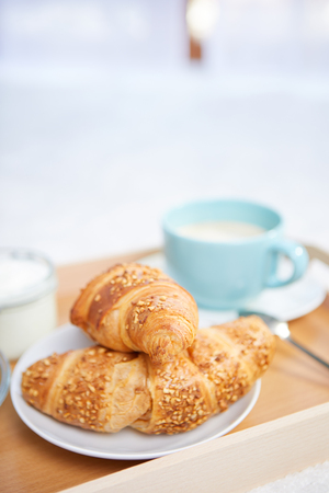 breakfast in bed with coffee and croissants