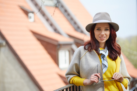 Outdoor fashion portrait of pretty stylish laughing woman in grey wool hat.Yellow jacket, overall , bright make up, European street background. Street look. Enjoy weekends. Stock Photo